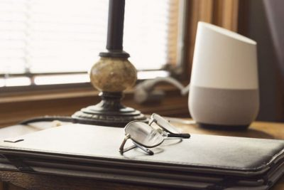 Google Home on a table with a notebookth glasses and