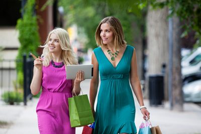 women shopping holding their device for a digital retail experience